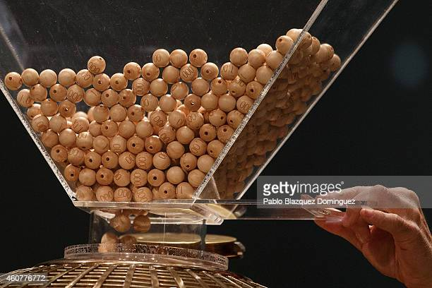 An official empties a recipient filled with balls bearing prizes into a ball recipient during the start of the draw of Spain's Christmas lottery...