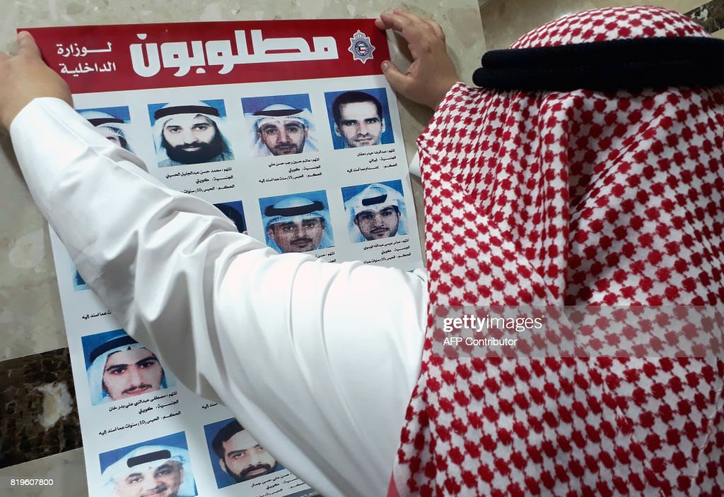 An official from Kuwait's interior ministry puts up a poster on July 20, 2017 in a Citizen Service Centre in Kuwait City, of fugitives convicted of belonging to a cell that had been formed and trained by Iran's Revolutionary Guards who were accused of plotting attacks in the state. Kuwait expelled Iranian diplomats and closed some embassy missions after the emirate's top court convicted a 'terror' cell of links to the Islamic republic, prompting Iran to threaten reciprocal measures. / AFP PHOTO / Yasser Al-Zayyat