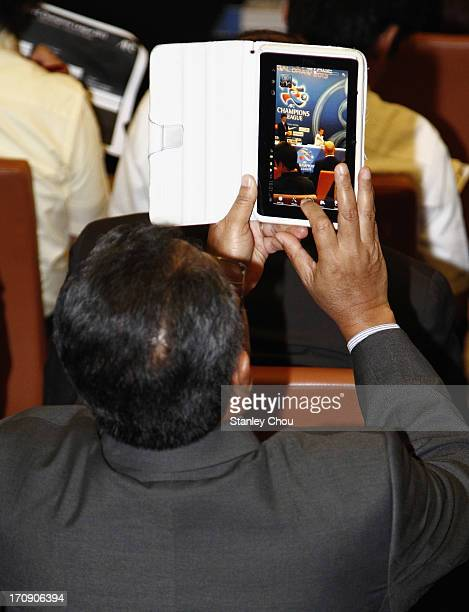An Official from the audience takes pictures of the draw with an ipad during the 2013 AFC Champions League Quarter Finals Knockout Stage Draw at the...