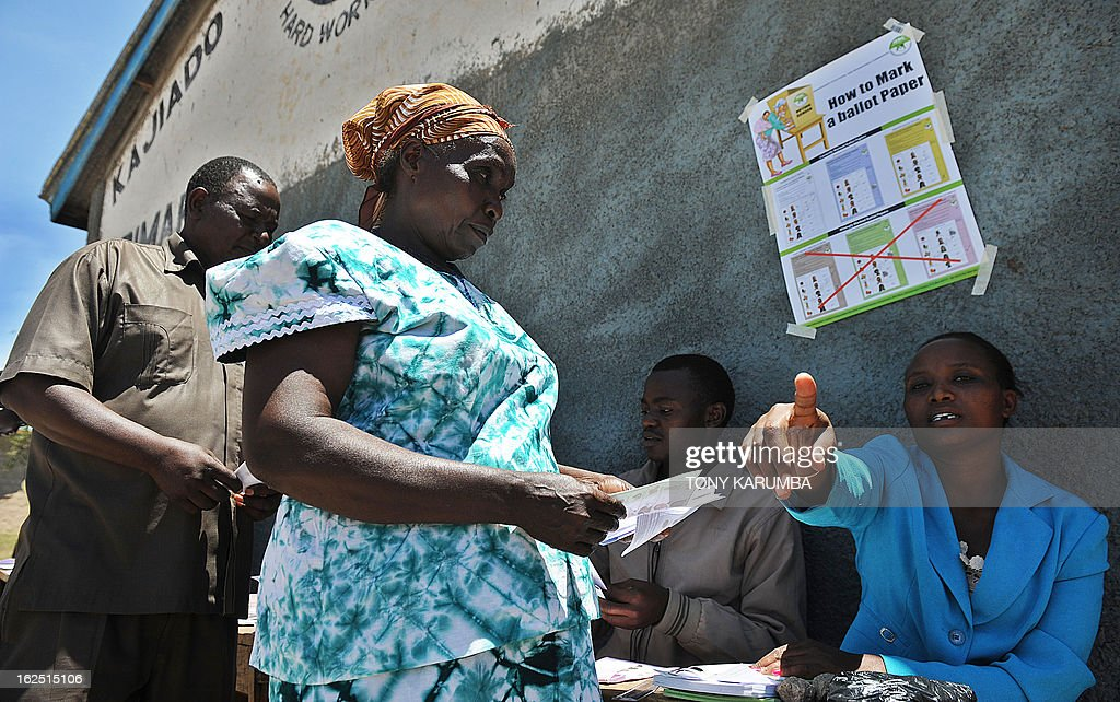 An official from the Independent Electoral and Boundaries Commission (IEBC) directs a Kenyan voter during a mock-election at a polling station in Kajiado, some 130 km southwest of Nairobi on February 24, 2013. The IEBC run the rehearsal eight days from Kenya's national elections viewed with an equal share of emotion and apprehension both locally and internationally and will be the first since bloody post-poll ethnic clashes that resulted in more than a thousand deaths. Presidential candidates in next week's poll made a rare show of unity to rally Kenyans to vote peacefully and avoid violence witnessed during the last general election. AFP PHOTO/Tony KARUMBA