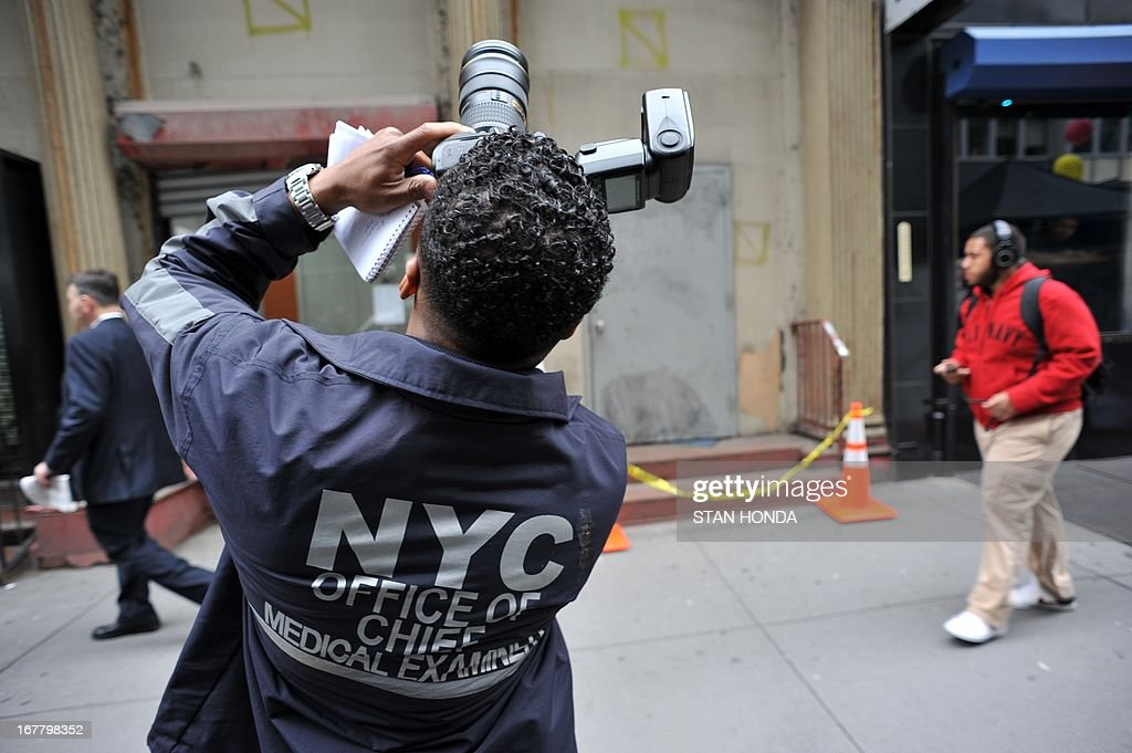An official from the New York City Medical Examiners Office takes photographs outside a site April 30, 2013 in Lower Manhattan where New York police said that they have found a fragment of one of two airplanes that slammed into the World Trade Center on September 11, 2001. The fragment was found April 27 and the medical examiner will be searching for possible human remains before the part of the plane is removed. AFP PHOTO/Stan HONDA