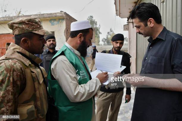 An official from the Pakistan Bureau of Statistics collects information from a resident during a census as security personnel guard them in Peshawar...