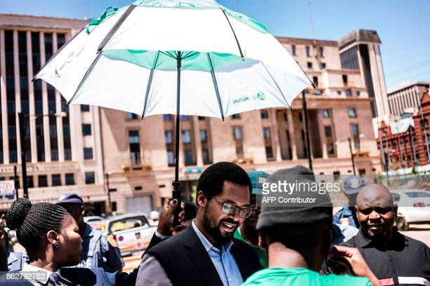 An official from the South African department of the Treasury is sheltered from the sun by an usher holding an umbrella while receiving a memorandum...
