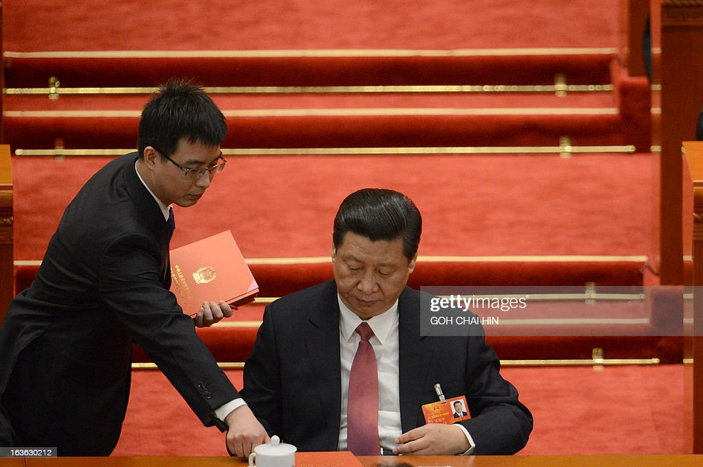 An official hands Chinese Vice President Xi Jinping the ballot papers prior to the election for the new president of China during the 12th National People's Congress (NPC) in the Great Hall of the People in Beijing on March 14, 2013. China's parliament is to name Xi Jinping as the country's new president on March 14, formalising his leadership of the world's most populous nation four months after he took charge of the ruling Communist Party. AFP PHOTO /GOH CHAI HIN