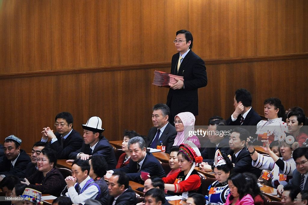 An official hands out ballot papers during the 12th National People's Congress (NPC) in the Great Hall of the People in Beijing on March 14, 2013. China's parliament is to name Xi Jinping as the country's new president on March 14, formalising his leadership of the world's most populous nation four months after he took charge of the ruling Communist Party.