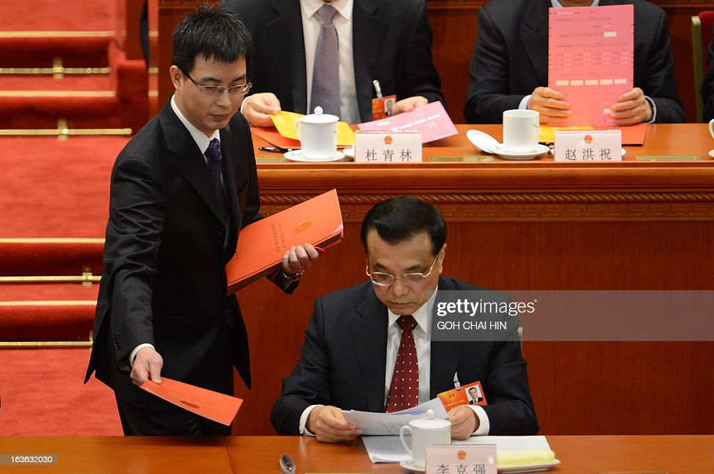 An official hands to Chinese Vice Premier Li Keqiang the ballot papers prior to the election for the new president of China during the 12th National People's Congress (NPC) in the Great Hall of the People in Beijing on March 14, 2013. China's parliament is to name Xi Jinping as the country's new president on March 14, formalising his leadership of the world's most populous nation four months after he took charge of the ruling Communist Party.