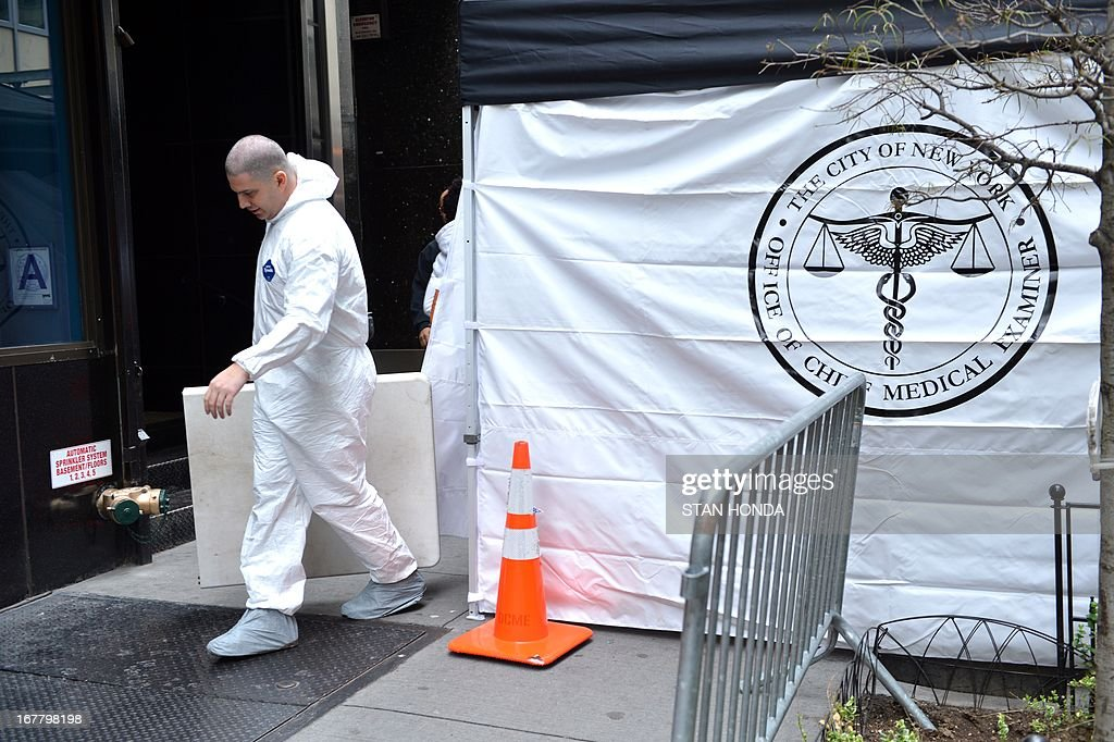 An official (C) in a protective white suit from the New York City Medical Examiners Office, enters a site April 30, 2013 in Lower Manhattan where New York police said that they have found a fragment of one of two airplanes that slammed into the World Trade Center on September 11, 2001. The fragment was found April 27 and the medical examiner will be searching for possible human remains before the part of the plane is removed. AFP PHOTO/Stan HONDA