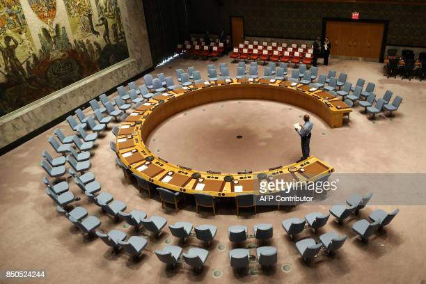 An official looks at the empty chair of leaders ahead of their participation in an open debate of the United Nations Security Council in New York on...