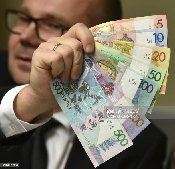 An official of Belarus' National Bank shows the new Belarus' ruble banknotes during a presentation in Minsk on November 10 2015 Belarus will slash...