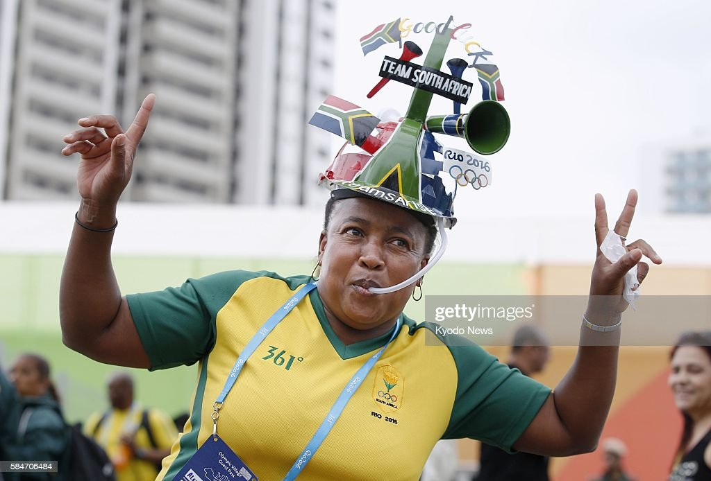 An official of South Africa's women's soccer team wears a 'makarapa' a decorated hard hat often worn by the country's sports fans at the Olympic...
