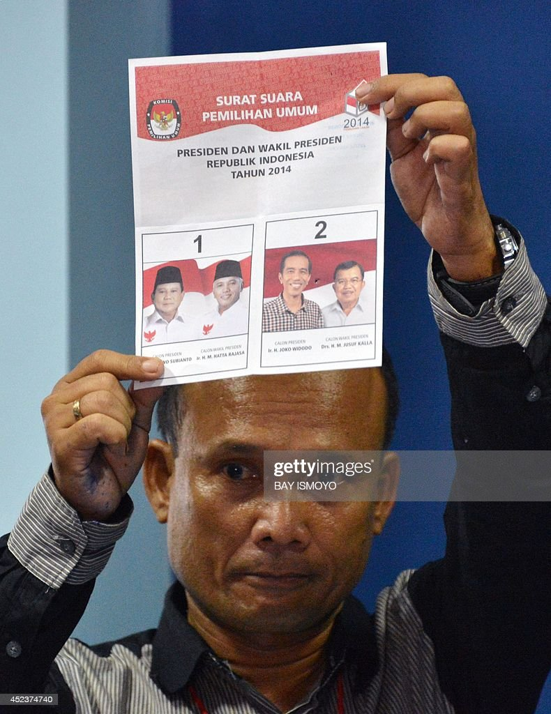 An official of the general election commission displays a cast ballot paper during the tabulation of re-voting in Jakarta on July 19, 2014, as part of the re-vote at several places by the Jakarta general election commission based on reports filed by presidential candidate Prabowo Subianto's campaign team who suspected there were election violations at 5,841 polling stations in Indonesia's capital city. Two Indonesian polling agencies which predicted a win for Prabowo Subianto in last week's bitterly fought presidential election were expelled from the main industry body after refusing to undergo an audit. AFP PHOTO / Bay ISMOYO