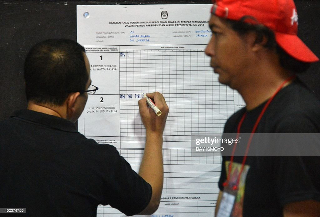 An official of the general election commission tallies the tabulation result of re-voting in Jakarta on July 19, 2014, as part of the re-vote at several places by the Jakarta general election commission based on reports filed by presidential candidate Prabowo Subianto's campaign team who suspected there were election violations at 5,841 polling stations in Indonesia's capital city. Two Indonesian polling agencies which predicted a win for Prabowo Subianto in last week's bitterly fought presidential election were expelled from the main industry body after refusing to undergo an audit. AFP PHOTO / Bay ISMOYO