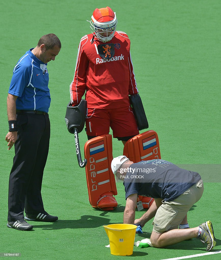 An official (front R) scrubs blood off the pitch after Robbert Kempermann of The Netherlands was hit in the head by Shafqat Rasool of Pakistan during the first semi final at the men's Hockey Champions Trophy in Melbourne on December 8, 2012. IMAGE STRICTLY RESTRICTED TO EDITORIAL USE - STRICTLY NO COMMERCIAL USE AFP PHOTO/Paul CROCK