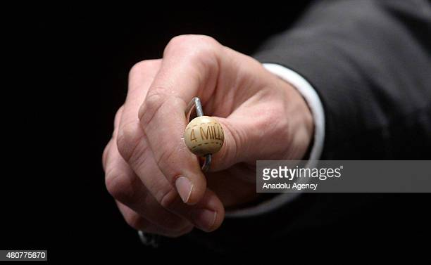 An official shows the 4millioneuro lottery ball to press members and audiences during the Spanish Christmas Lottery draw at Madrid's Royal Theatre...