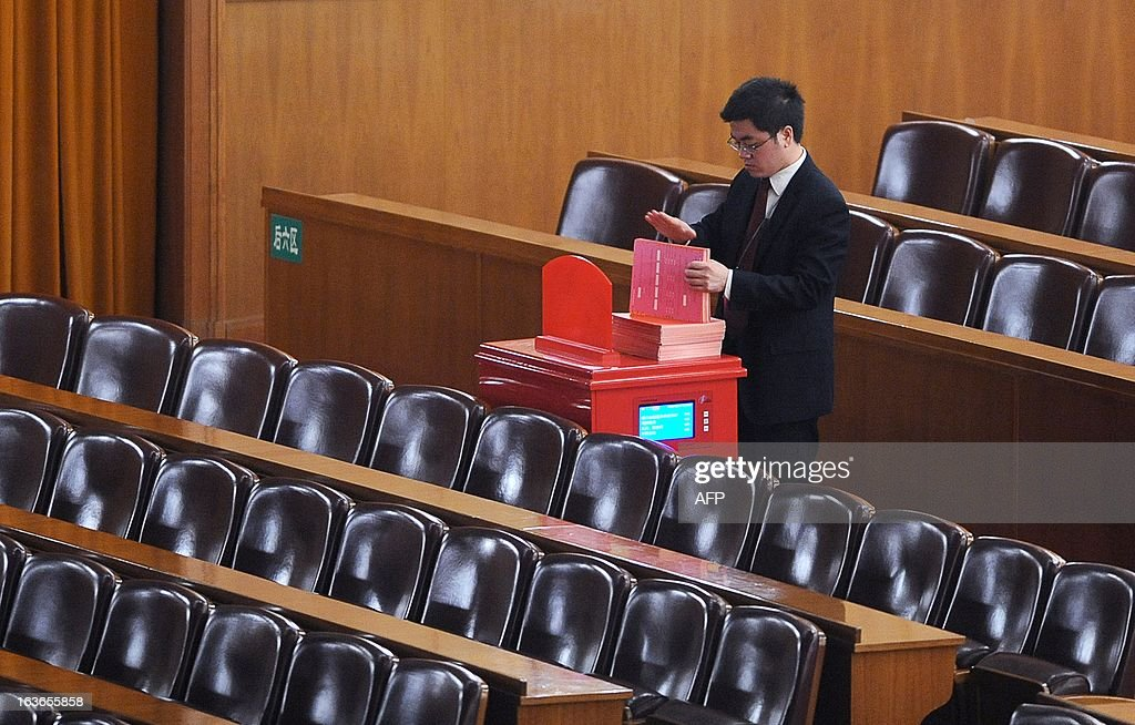 An official takes the ballot papers out from a ballot box after the election for the new president of China during the 12th National People's Congress (NPC) at the Great Hall of the People in Beijing on March 14, 2013. China's parliament named Xi Jinping as president on March 14, four months after he took charge of the Communist Party with pledges of reform that have raised hopes but so far yielded little change.