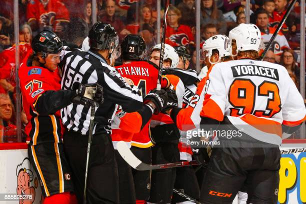 An official tries to stop a fight in a game of the Calgary Flames against the Philadelphia Flyers at the Scotiabank Saddledome on December 04 2017 in...