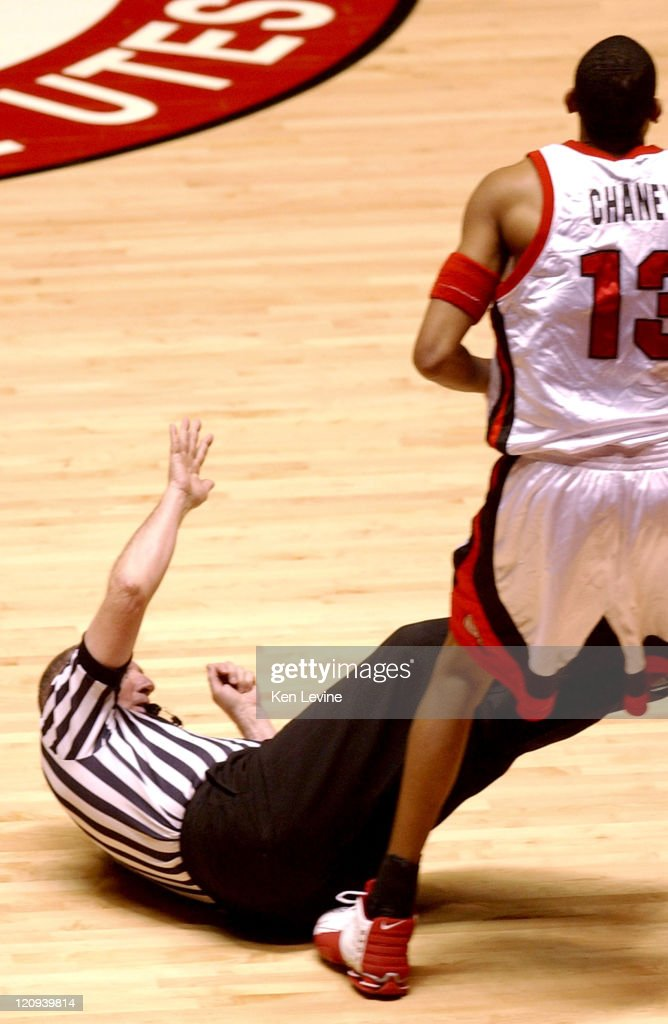 An official tumbles to the floor following an unintentional collision with Utah forward Richard Chaney (13). Utah defeated San Diego State 72-60 at the Jon Huntsman Center in Salt Lake City, Utah, on March 5, 2005.