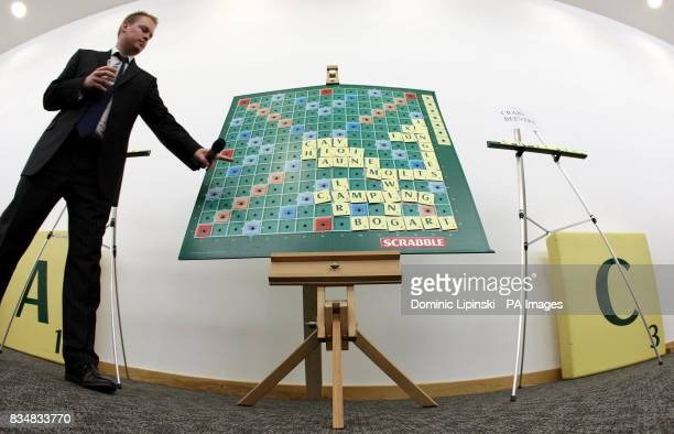 An official updates a giant scrabble board showing the final of the 37th National Scrabble Championships at the Cavendish Conference Centre London
