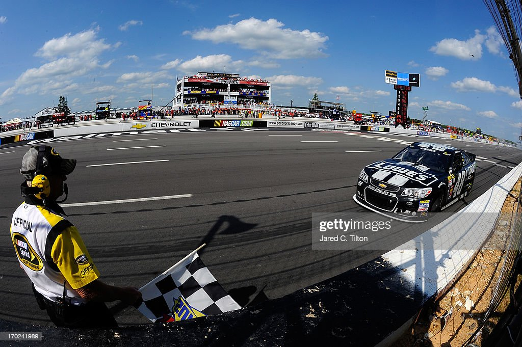 An official waits to hand Jimmie Johnson, driver of the #48 Lowe's/Kobalt Tools Chevrolet, the checkred flag after he won the NASCAR Sprint Cup Series Party in the Poconos 400 at Pocono Raceway on June 9, 2013 in Long Pond, Pennsylvania.