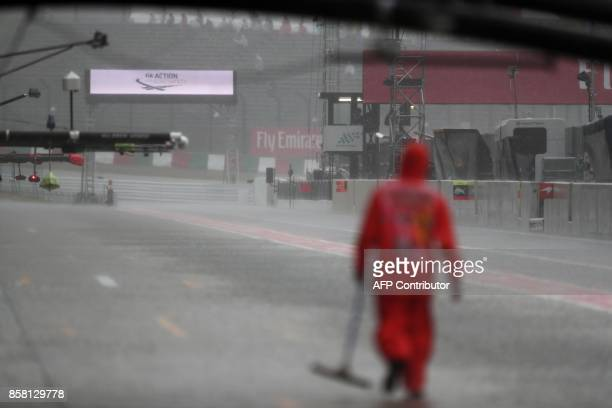 An official walks in the pit lane as heavy rain delays the second practice round of the Formula One Japanese Grand Prix at Suzuka on October 6 2017 /...