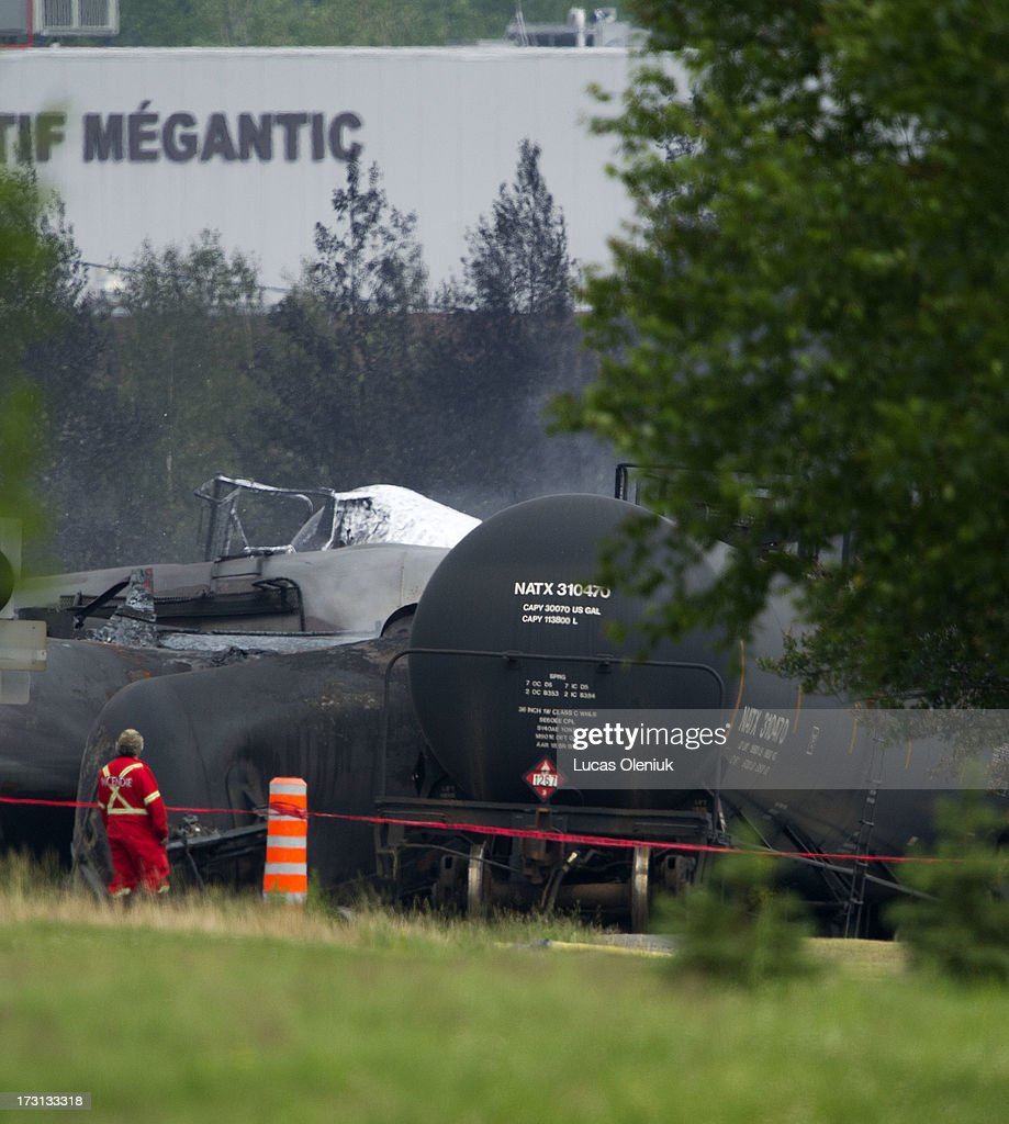 An official walks passed the derailed train in LacMÈgantic The heavily damaged area is being treated as a crime scene by investigers Five people have...