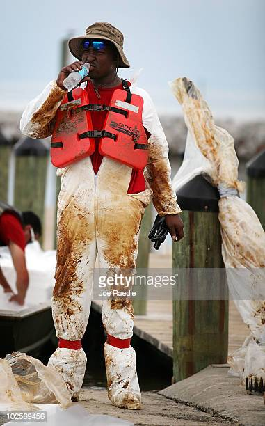 An oil cleanup worker is coated in oil as he helps remove residue washing ashore from the Deepwater Horizon oil spill in the Gulf of Mexico on July 1...