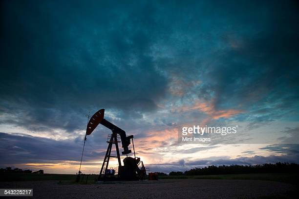 An oil derrick, a well head pump arm with frame, silhouetted against the evening sky. Oil business.