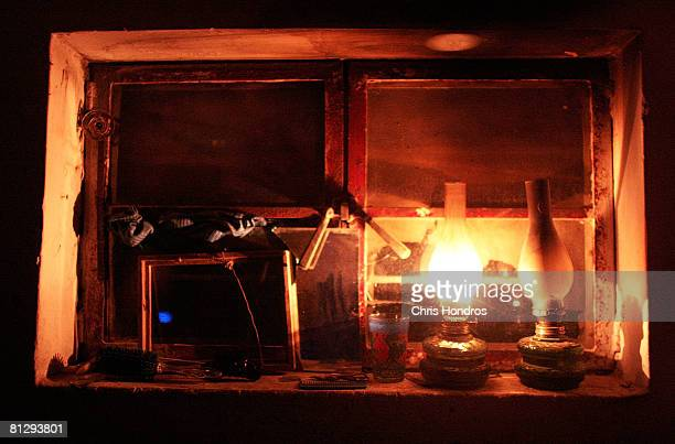 An oil lamp burns on a window ledge in the house of rural Iraqi farmers during an overnight raid by US troops May 14 2008 in Baghdad Iraq The US...