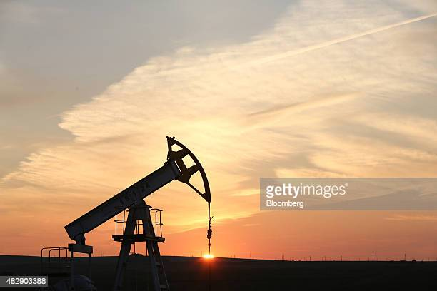 An oil pumping unit also known as a 'nodding donkey' or pumping jack operates at sunset at a drilling site operated by Tatneft OAO near Almetyevsk...