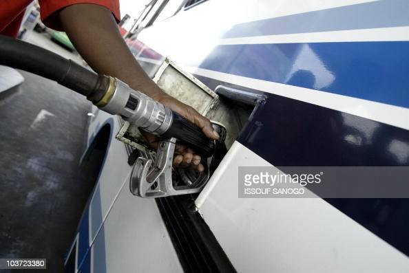 An oil station worker fills the tank 19 October 2004 in Abidjan where oil prices have risen from 10 to 38 per cent This rise followed Ivorian...