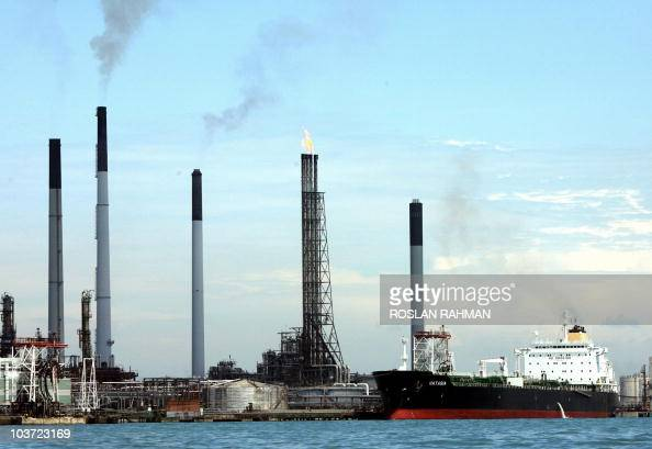 An oil tanker berth next to a refinery on an island off Singapore 12 April 2006 Oil prices fell in Asian trading on profittaking after surging to...