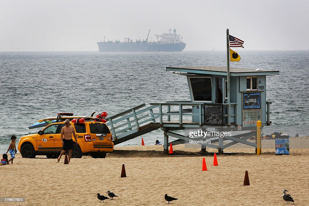 An oil tanker unloading to the Chevron El Segundo refinery, sits on the horizon, as a man walks by a lifeguard tower in Manhattan Beach, California, U.S., on Wednesday, Aug. 14, 2013. Overall U.S. tourism-related sales increased 6.8% in the second quarter of 2013 as compared to 2012. Photographer: Patrick T. Fallon/Bloomberg via Getty Images