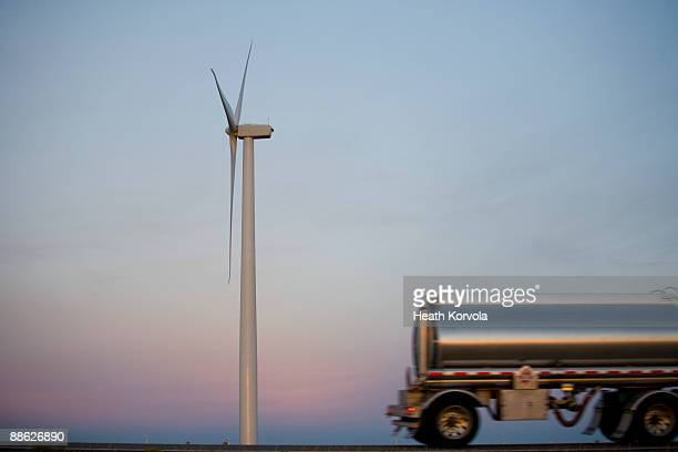 An oil truck passes a wind turbine at sunset.