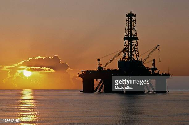 An oil well with cranes in the sea at dusk in Texas