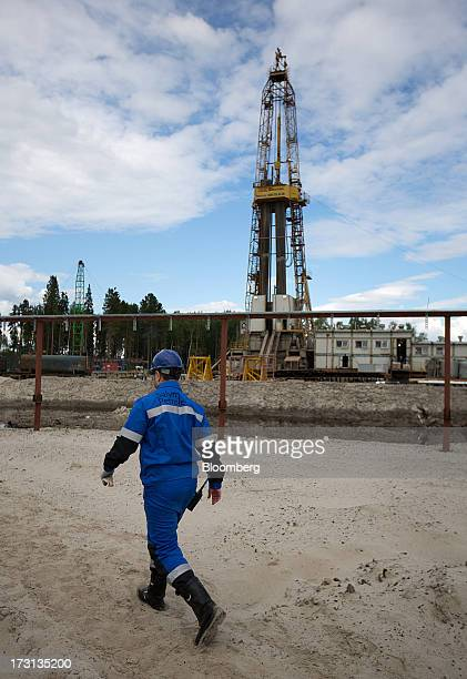 An oil worker passes a derrick operated by Salym Petroleum in Salym KhantyMansi autonomous region Russia on Tuesday July 2 2013 Gazprom Neft and...