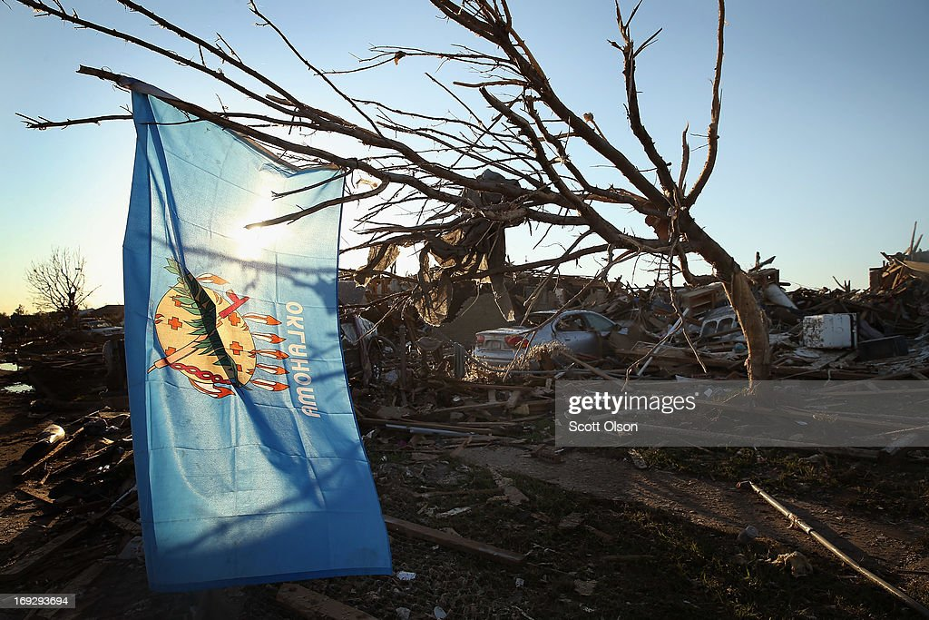An Oklahoma state flag hangs in a tree next to a destroyed home across the street from the Plaza Towers Elementary School where several children died during a tornado that ripped through the area on May 22, 2013 in Moore, Oklahoma. The tornado of at least EF4 strength and two miles wide touched down May 20 killing at least 24 people and leaving behind extensive damage to homes and businesses. U.S. President Barack Obama promised federal aid to supplement state and local recovery efforts.