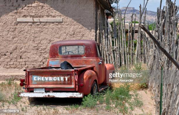 An old abandoned pickup truck sits in the weeds beside an abandoned adobe church building at San Ildefonso Pueblo in New Mexico near Los Alamos...