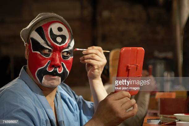 An old actor holds a mirror in front of his face and carefully applies traditional Chinese face paint to his eyebrow.