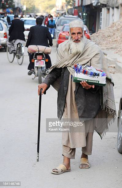 An old Afghan male street vendor walks with his commodities in Chicken Street on October 17 2011 in Kabul Afghanistan Chicken Street has been a focus...