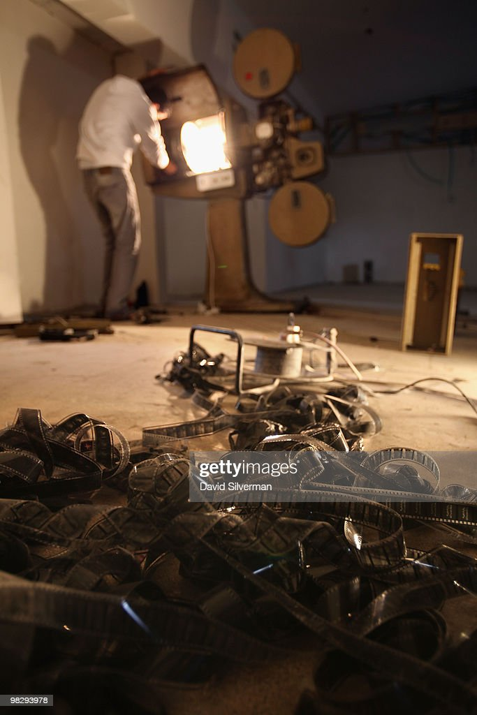 An old Arabic black-and-white movie lies on the floor as Ma'moun Kanan, assistant manager of the Cinema Jenin project, and , his compatriot and the project, tries to operate one of the original projectors found during renovations of the city's old movie theatre on March 10, 2010 in Jenin, West Bank. Twenty-two years after it was closed during the first Palestinian intifada, German director Marcus Vetter and his team of local Palestinian staff and foreign volunteers, with funding from the German government, the Roger Waters foundation and other sponsors, are turning the run-down cinema into a modern cinematheque.