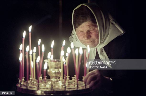 An old babushka lights a candle in the church of the Monastery of Sergiyev Posad during the religious service marking the Orthodox Easter on April 23...