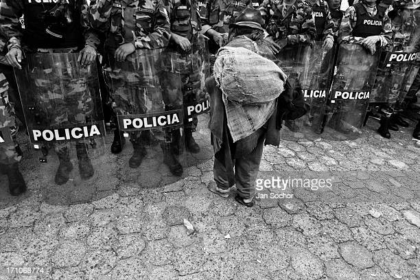 An old barefoot Indian passes through the riot police block during the Inti Raymi festivities on 29 June 2010 in Cotacachi Ecuador La toma de la...