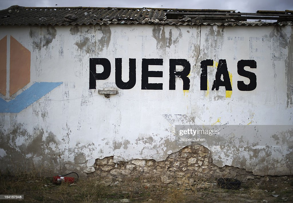 An old building stamped with the word puertas stands abondoned on October 12, 2012 in the small industrial town of Villacanas, Spain. During the boom years, where in its peak Spain built some 800,000 houses a year, more than Britain, Germany and France combined, and millions of wooden doors where needed, the people of Villacanas were part of a proud elite enjoying high wages and permanent jobs. Almost all of those doors used came from this small industrial town in the La Mancha province, some seven million a year, leaving with truck loads at the same time, from the now empty and silent Villacanas industrial park. With Spain in recession and the housing bubble busted, the door industry is shattered and unemployment in Villacanas, zero for nearly a generation, is rising fast.