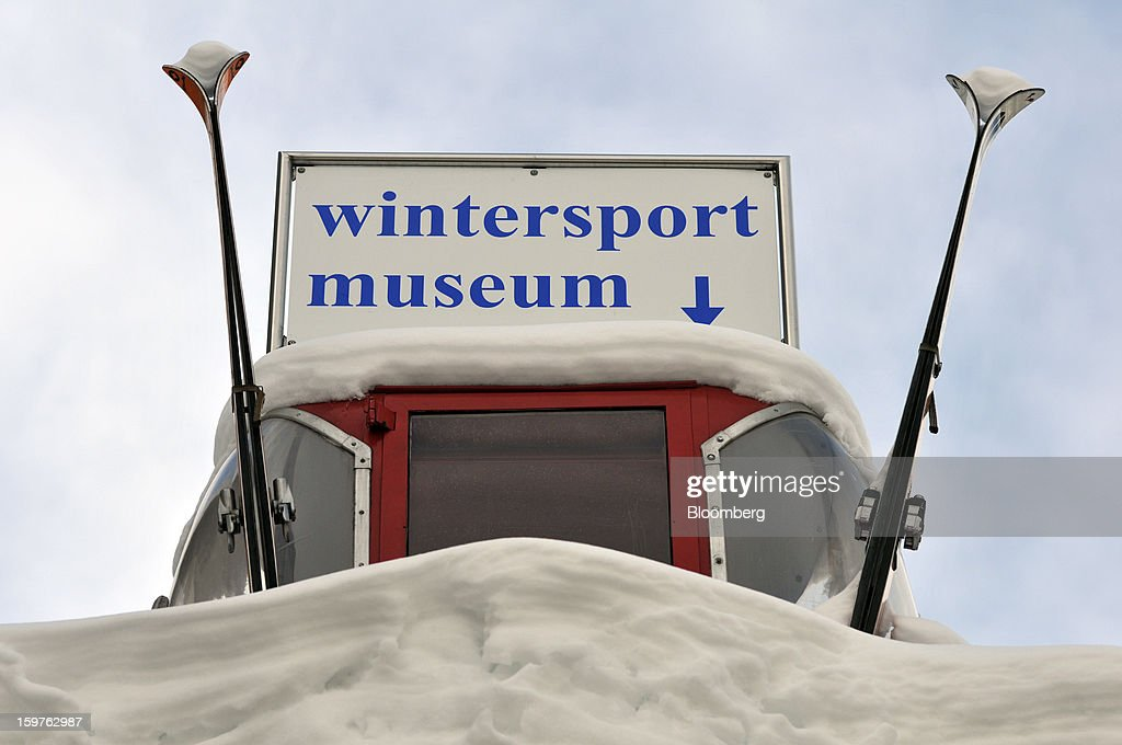 An old cable car gondola and skies sit covered in snow at the entrance to the Wintersport museum in the town of Davos, Switzerland, on Saturday, Jan. 19, 2013. Next week the business elite gathers in the Swiss Alps for the 43rd annual meeting of the World Economic Forum in Davos, the five day event runs from Jan. 23-27. Photographer: Bryn Colton/Bloomberg via Getty Images