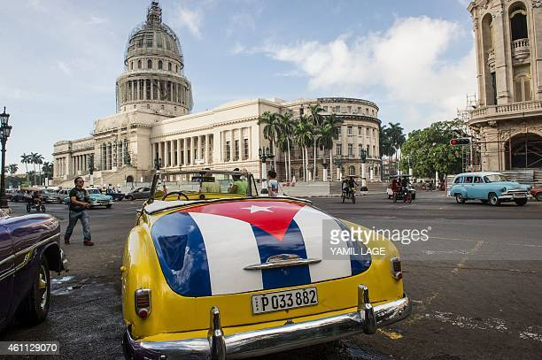 An old car with the Cuban flag painted on the trunk is seen near the Capitol of Havana on January 7 2015 Cuba's iconic stock of refurbished vintage...