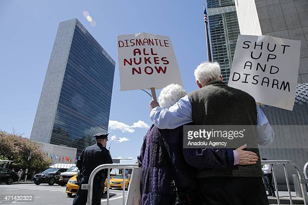 An old couple hold placards as they take part in a nuclear disarmament protest outside the United Nations headquarters in New York on April 28 2015