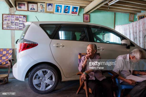 An old couple sits besides the family car parked inside the house entrance in Muse Myanmar border town with China