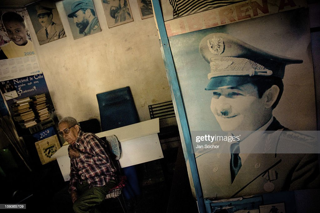 An old Cuban man sells propaganda books and posters of the revolutionary leaders in a second-hand book shop in Havana, Cuba, 15 February 2009 in Havana, Cuba. During the Cuban Revolution, an armed rebellion at the end of the 1950s, most of the revolutionary leaders started as unnamed soldiers fighting from the jungle. After taking over the power, they became autocratic rulers holding almost absolute power and pursuing the opposition. For some reason Cuban people never stopped to worship Fidel Castro, Che Guevara, Raul Castro and others. Cubans hang their photos and portraits on the wall at home, shops and working places even when they don't have to.