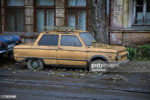 An old, dirty and rusty car parked on the side of a building
