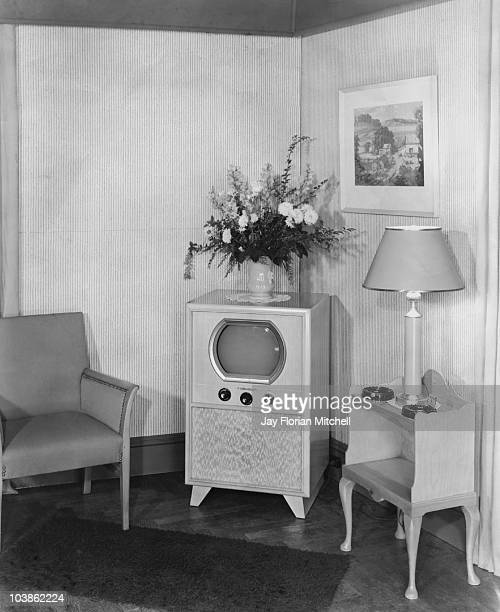 An old fashioned set situated in a corner of a living room setting with a flower arrangement in a vase on top of the television set USA circa 1945